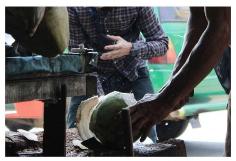 Seorang sedang memotong kelapa muda
